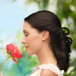 Woman with curled hair smelling flowers